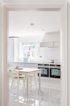 Doorway into a white shaker kitchen.