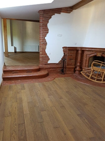 Hardwood and brick threshold between flooring and stairs.