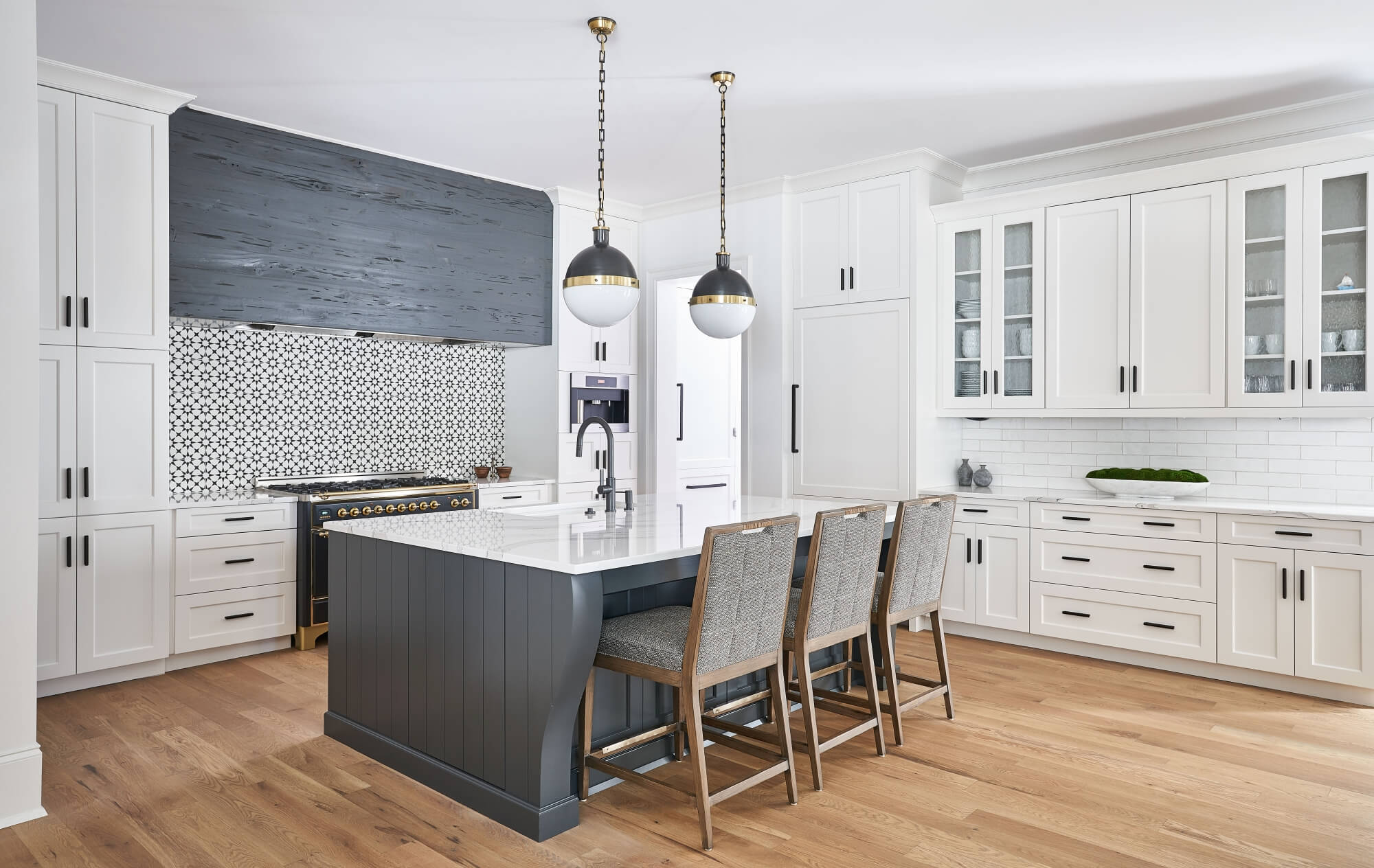 Beautiful light kitchen with natural wood flooring, white cabinets, and grey island and range hood.