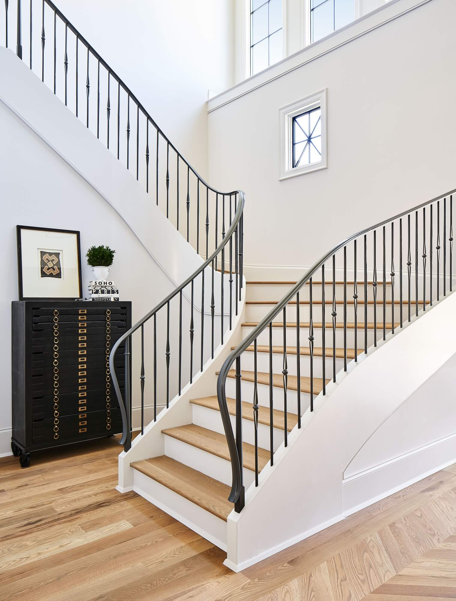 Large custom staircase in custom home with white oak flooring.