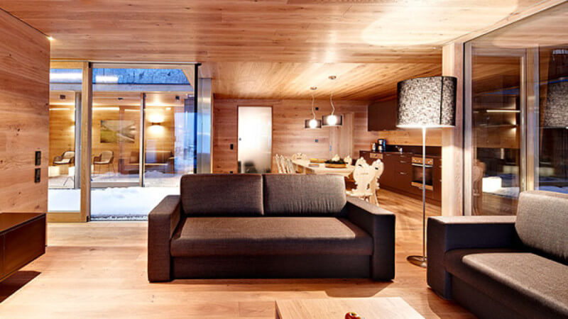 A warm ski resort with oak wood for the flooring, walls, and ceiling.