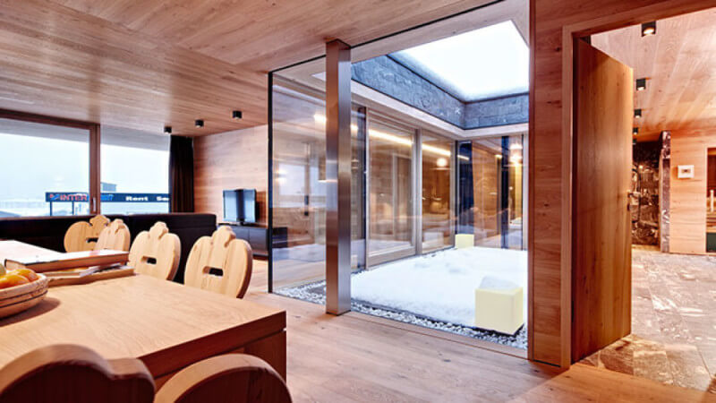 The warm atmospheric interior of a ski lodge featuring wooden walls, floors and ceilings.