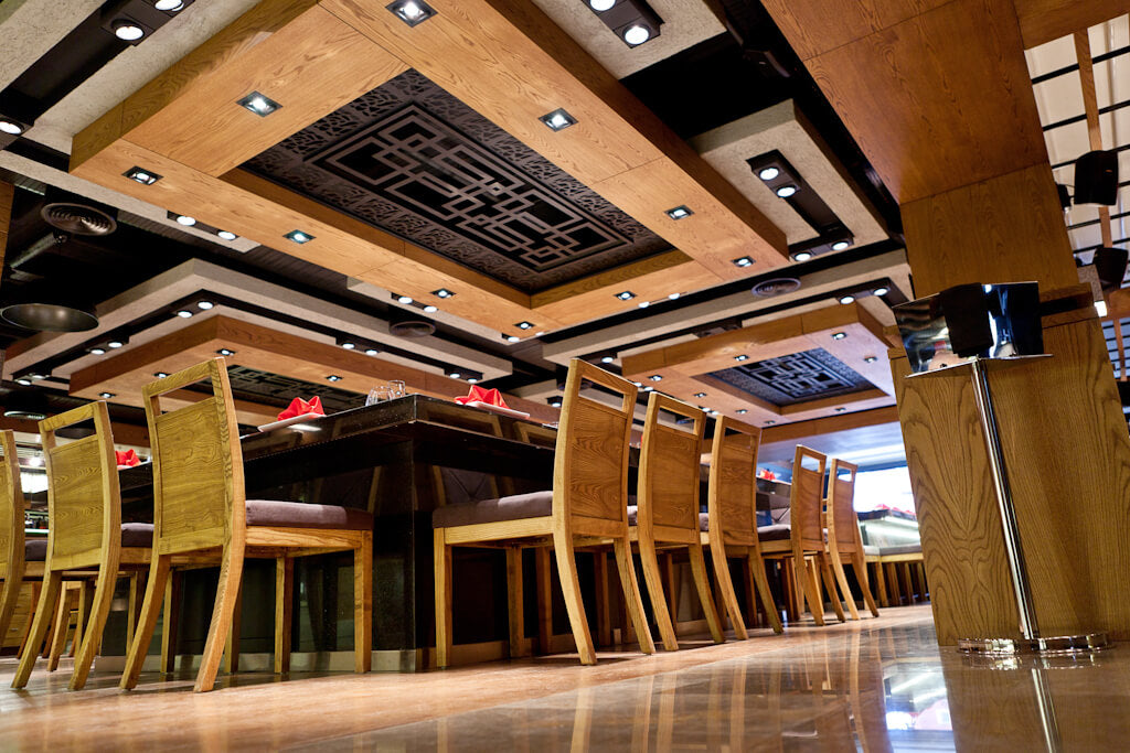 The ceiling in an asian restaurant has large wood panels and lighting.