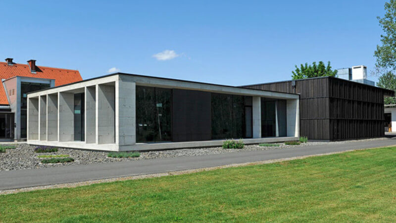 A view of a modern single-story home with wood panels and concrete.