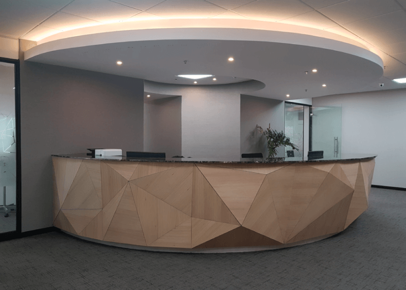 A curved reception desk with geometric wood shapes extruding from the front.