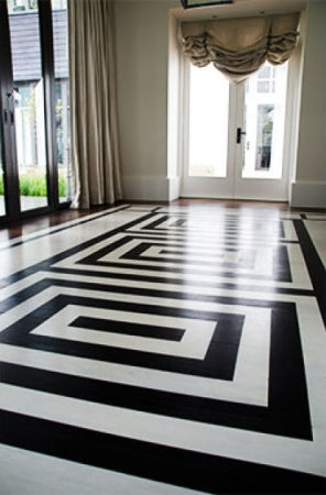 A black and white patterned floor with french doors leading outside.