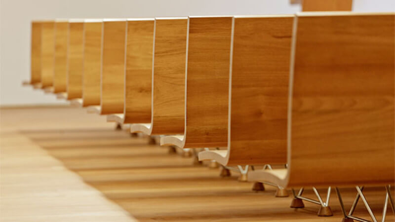 Rows of wood pews that are coated with the wood finish Rubio Monocoat.