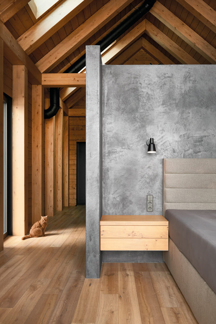 Wood and concrete bedroom design with vaulted ceiling.