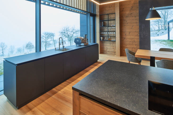 European oak wood flooring in kitchen with large windows looking over forest.