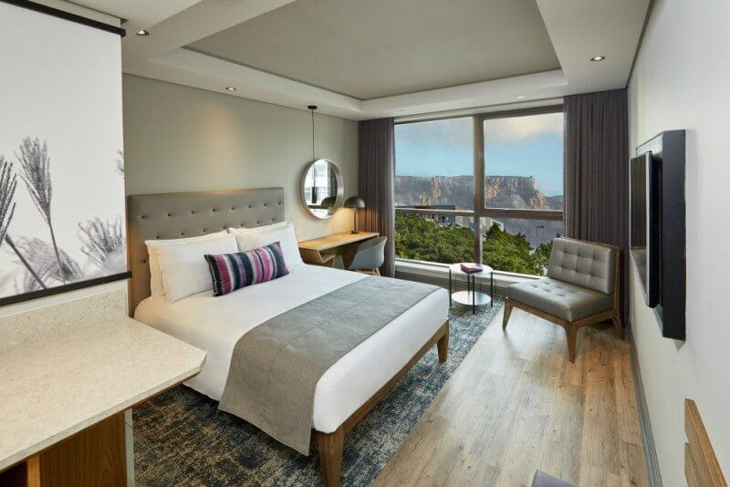 A hotel bedroom with hardwood flooring and a durable wood finish.