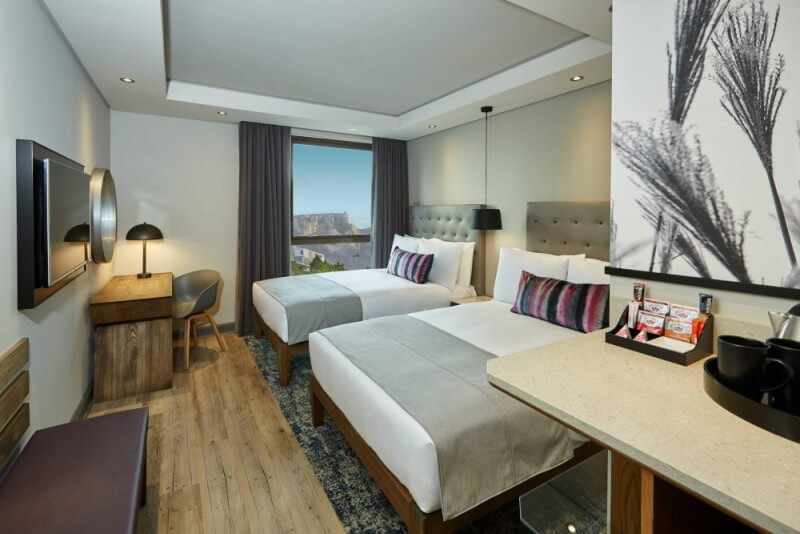 A hotel bedroom with wood flooring.