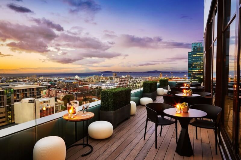 A beautiful hotel wood balcony overlooking the city during sunset.