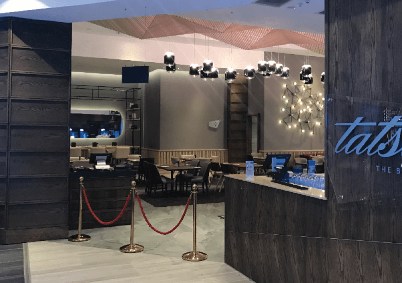 The entrance to a restaurant in a mall is made from wood panels that are finished with a beautiful wood finish.