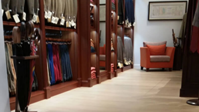 A clothing store with natural colored hardwood flooring throughout.