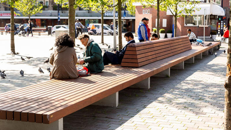 A wooden park bench with people sitting on the side.