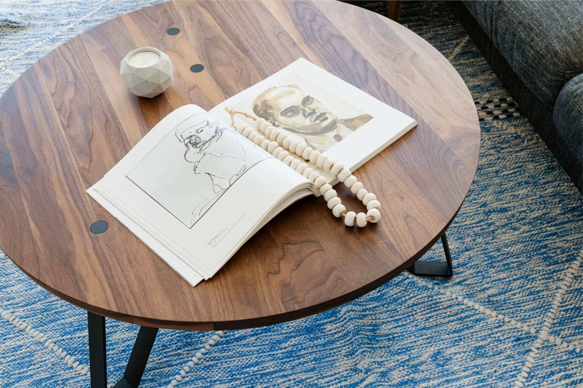 Round walnut coffee table on blue rug with a book on it.