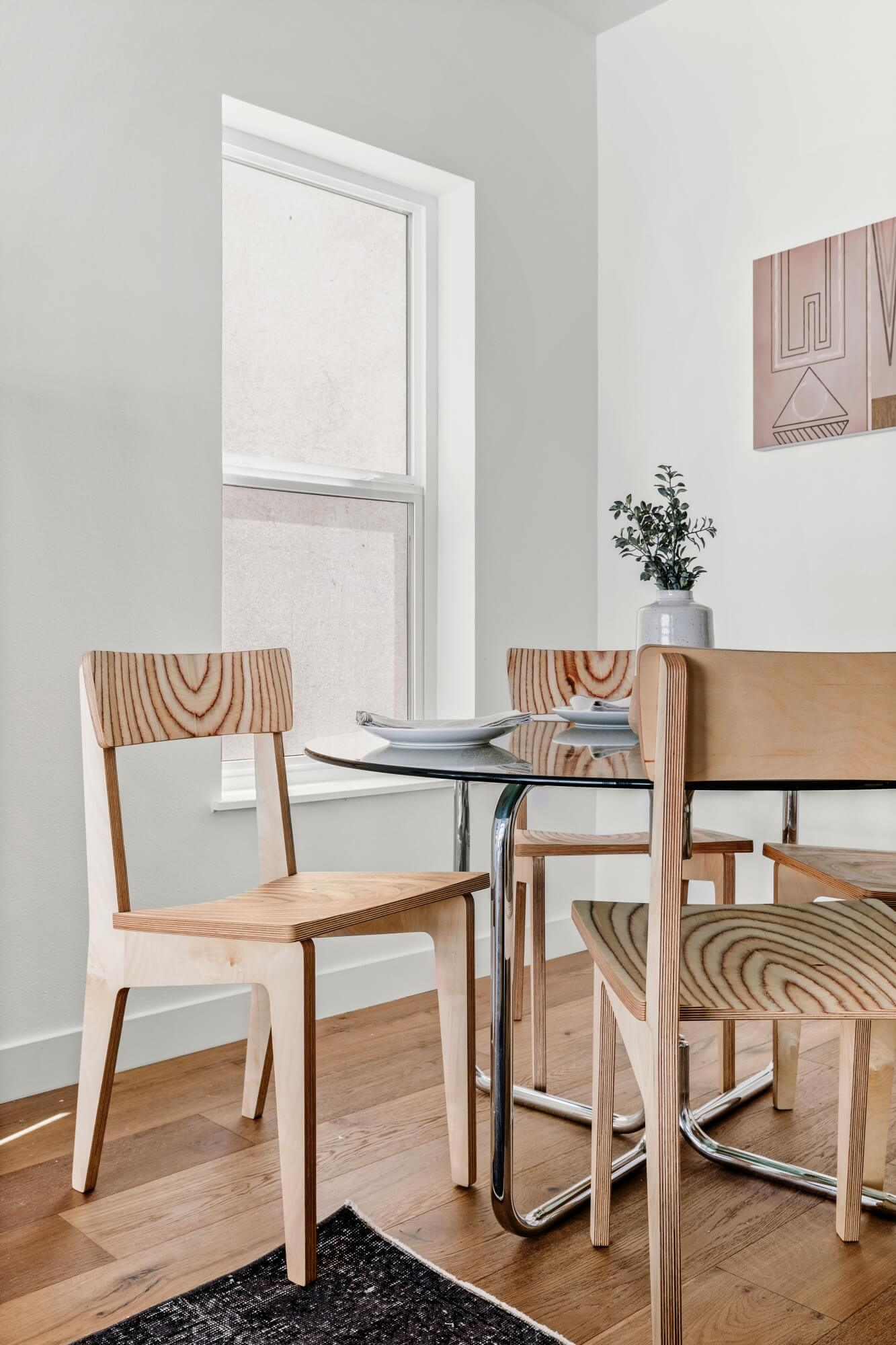Wood chairs at a glass dining table.