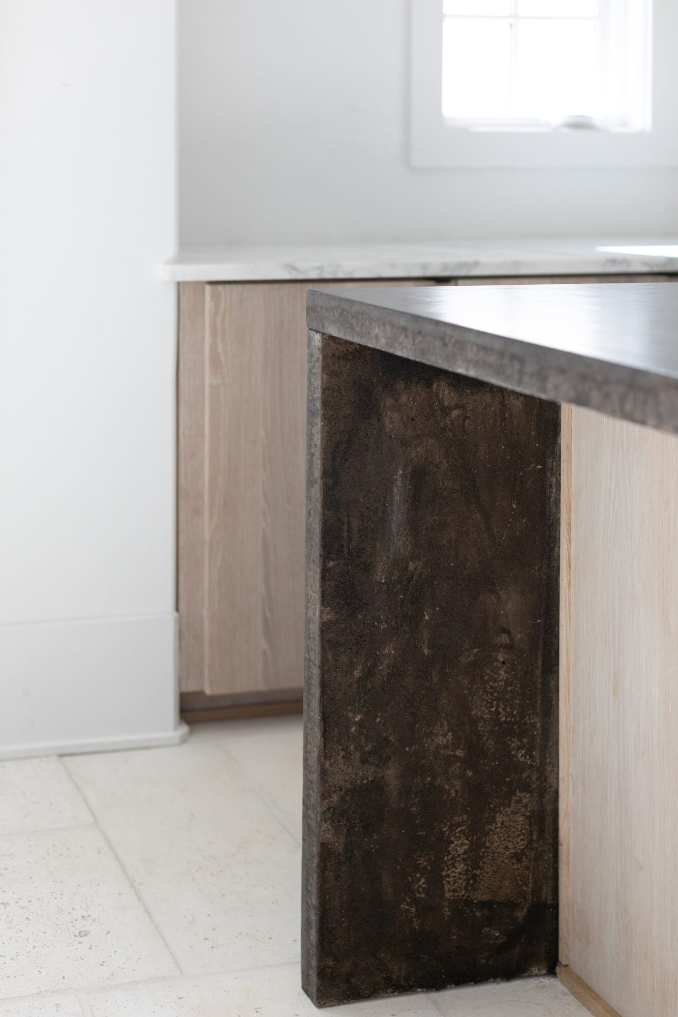 Detail photo of white oak kitchen island with dark waterfall counter tops.