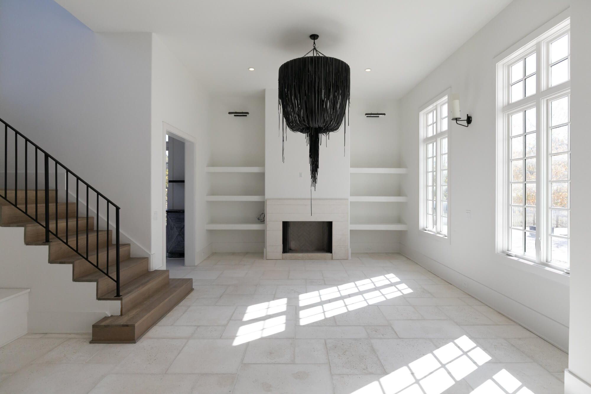 Light living room with grey wood stairs.