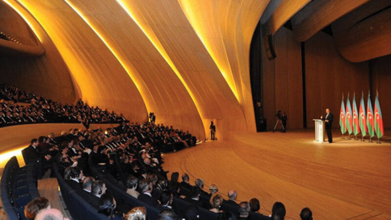 An audience watching a speaker in a large wood auditorium.