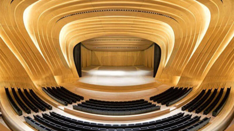 A symmetrical view of a large wood auditorium that has sweeping wood walls, recessed accent lighting, seating, and a massive wooden stage.