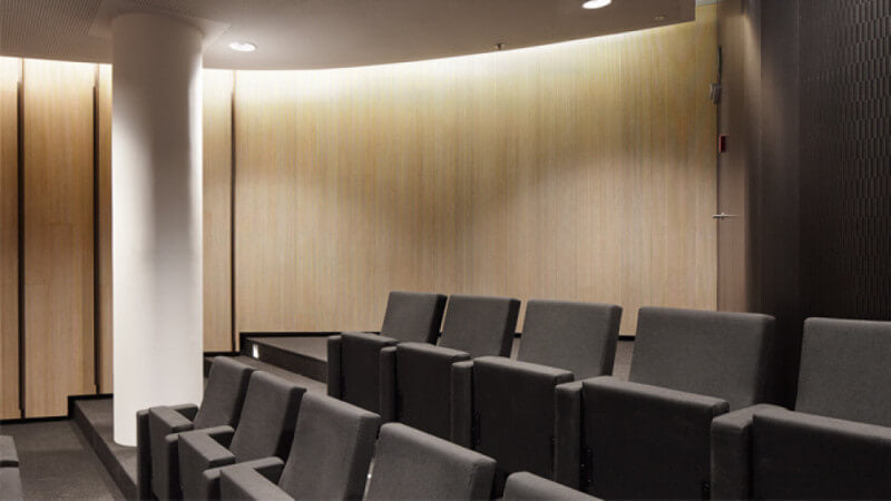 Seating and a wall of wooden acoustical panels that are treated with Rubio Monocoat hardwax oil wood finish.