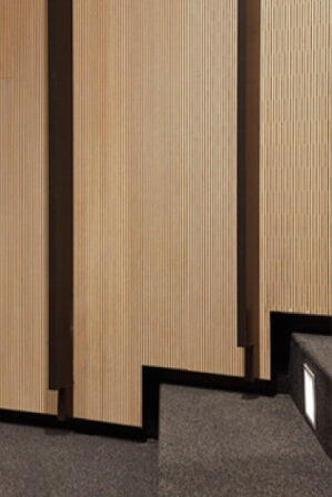 Acoustic wood paneling that contours steps in an auditorium.