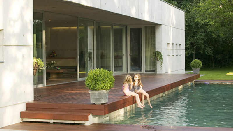 An oil finished Ipe deck beside a pool with 2 children soaking their feet in the pool.