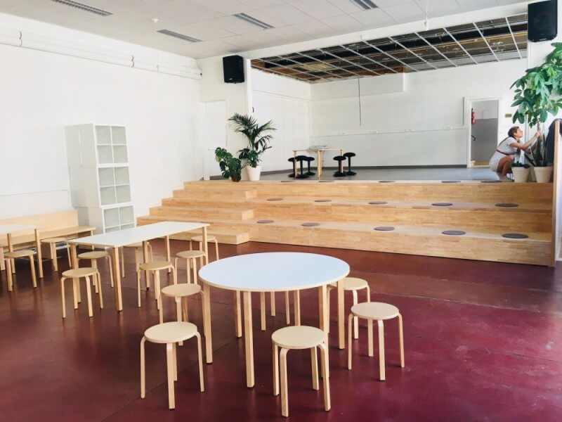 Tables and chairs in a school with a toy-friendly environmental wood finish on them.