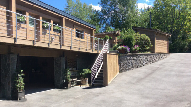 A driveway entering into a recently renovated wooden chalet.