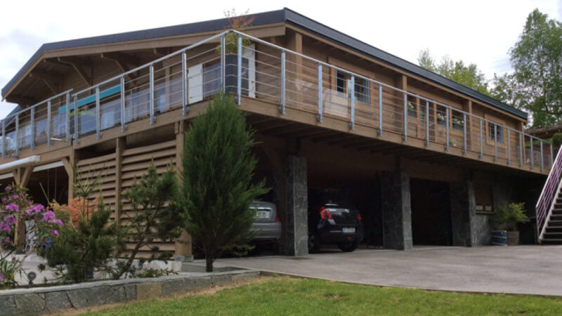 A restored wood cabin with a balcony around the upper level and a carport underneath the upper level.