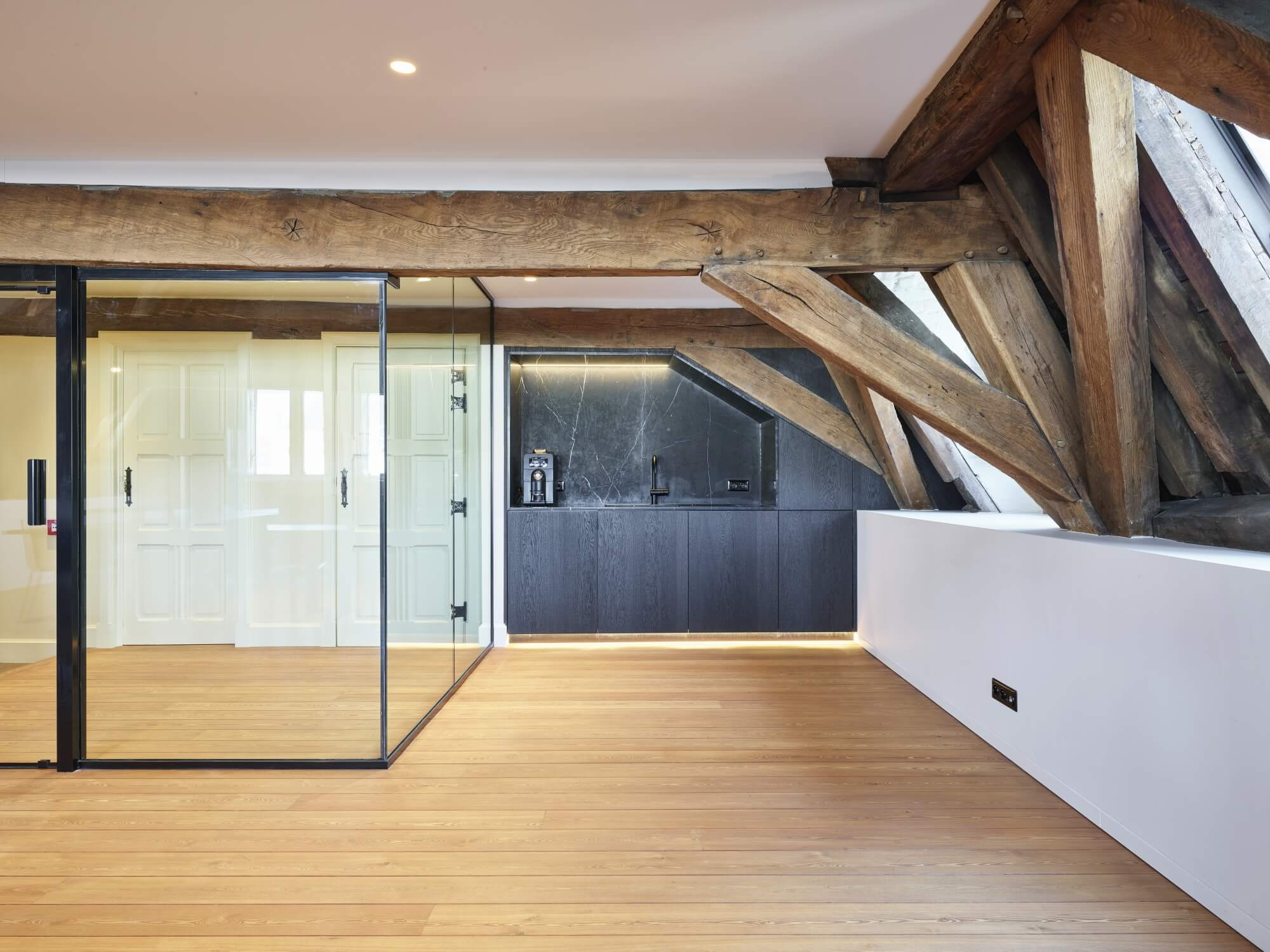 Office space with exposed wood beams, hardwood flooring and a glass rooms.