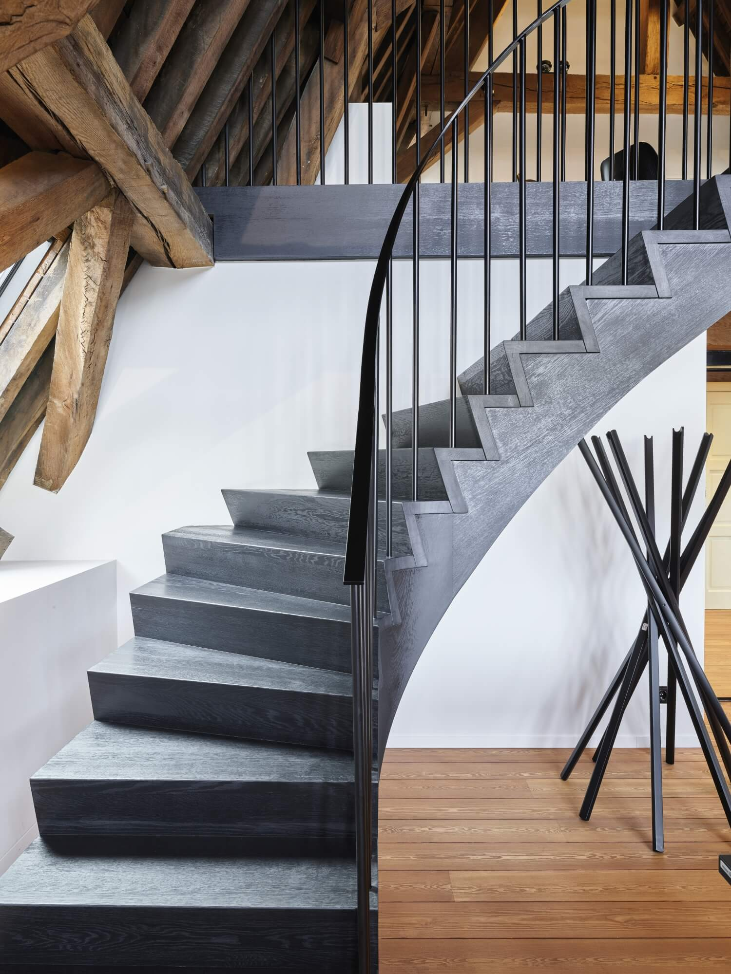 Curving black wood staircase.