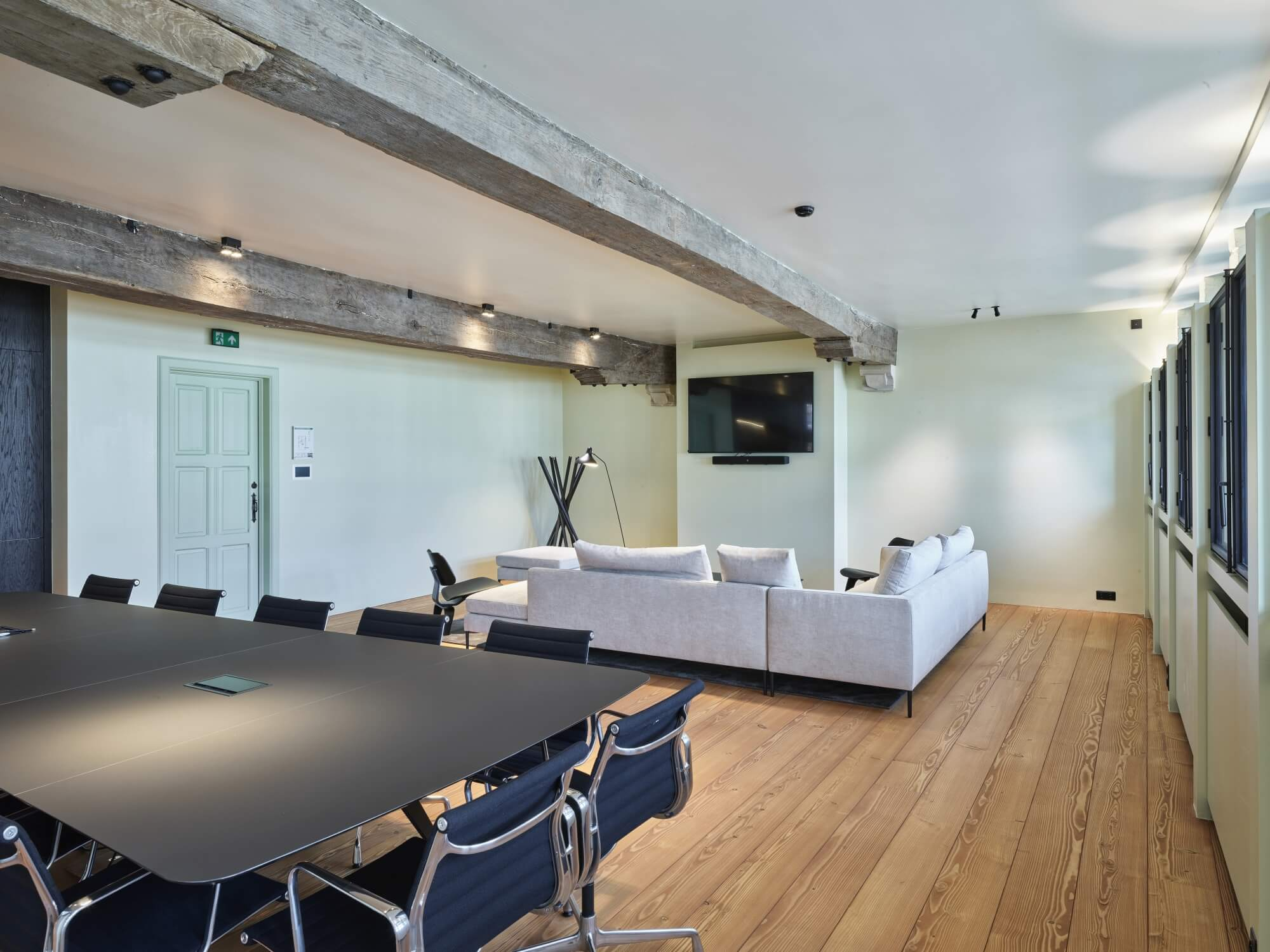 Conference room with conference table and couches and hardwood flooring.