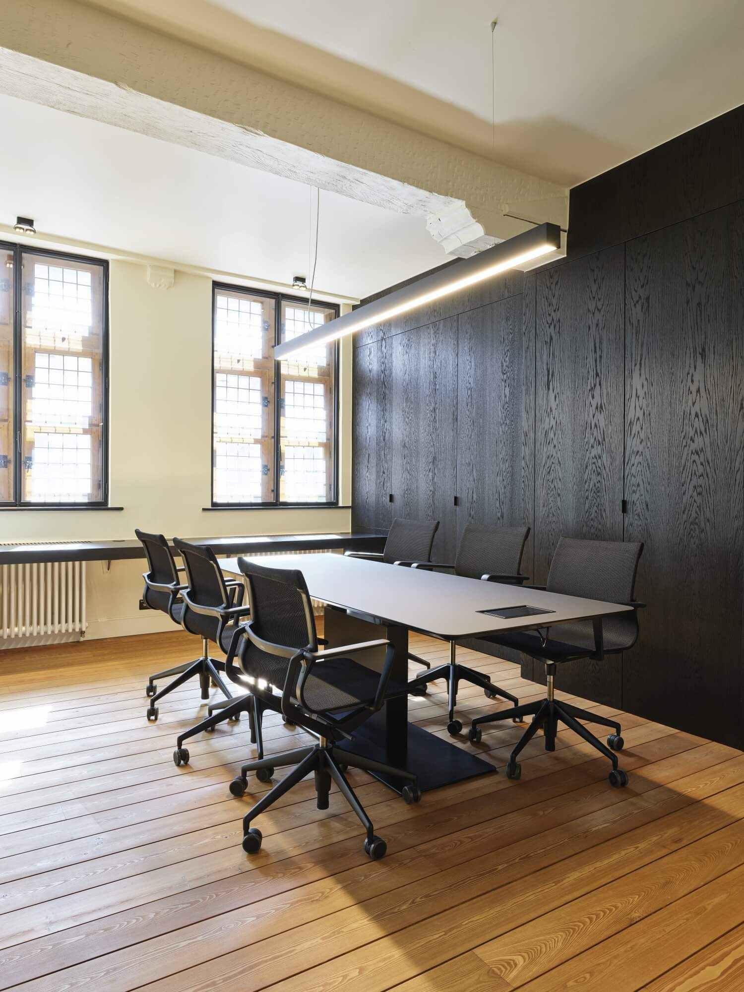 Matte wood floors in an office with large black wood wall cabinetry.