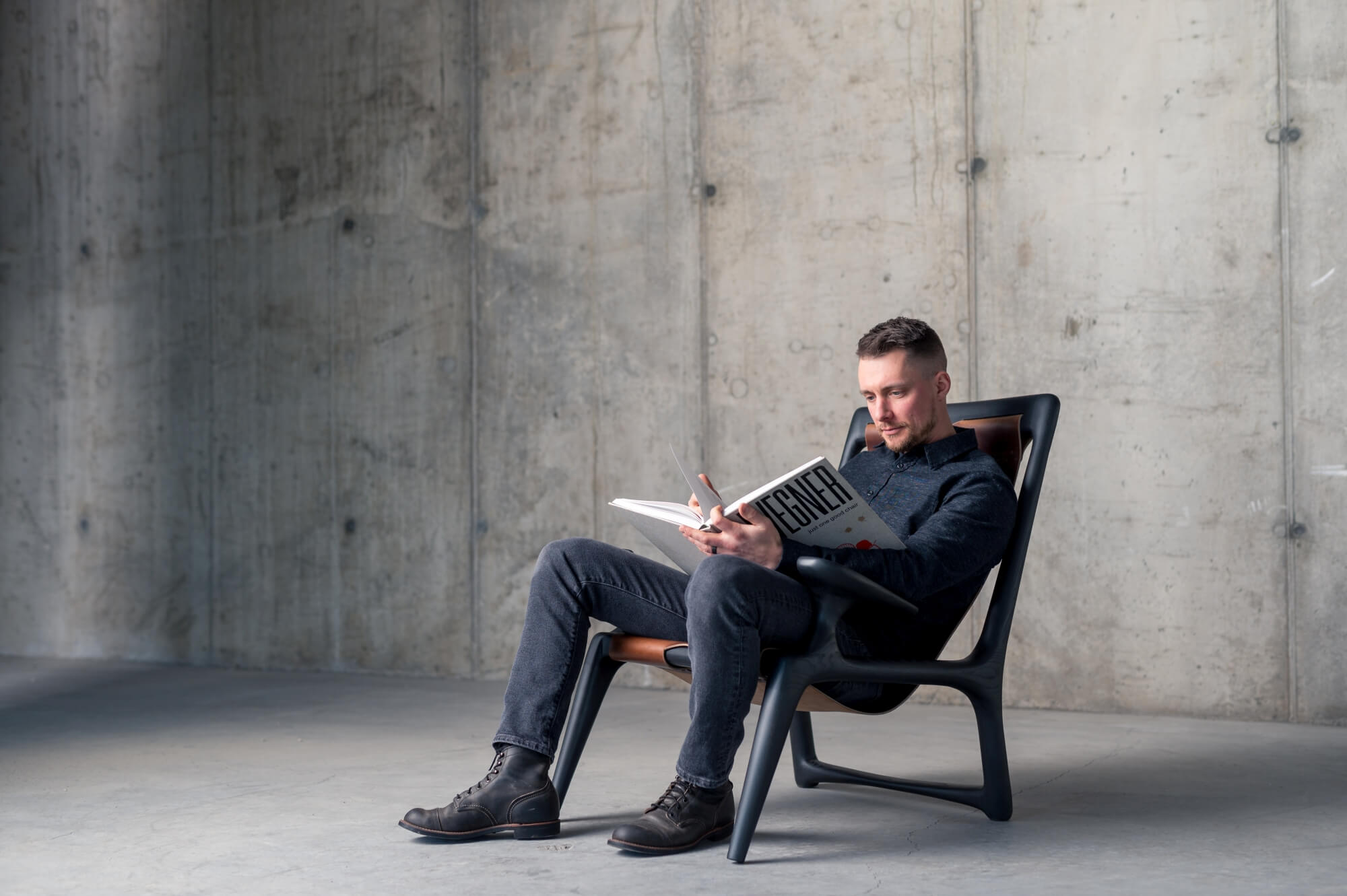 Man sitting in custom wood and leather chair reading a book.