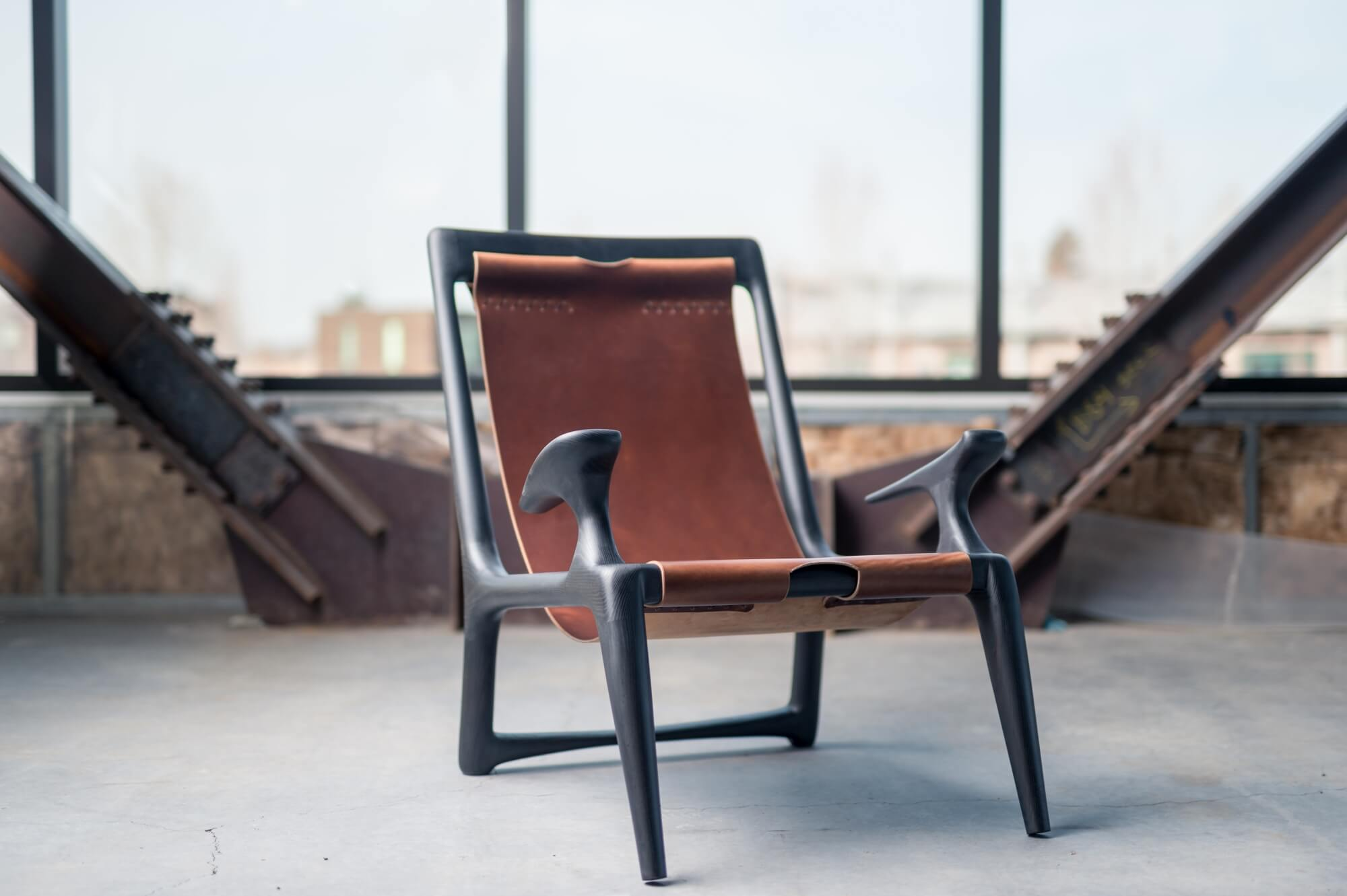 Custom wood chair with leather back sitting in a warehouse with large windows.