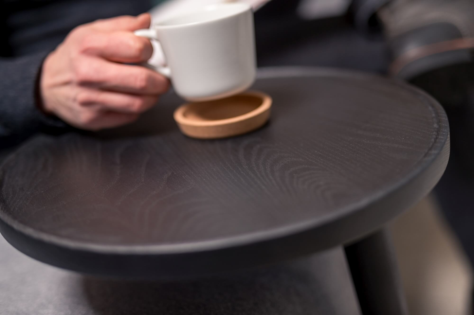 Ash coffee tray with a man sitting a coffee mug down on it.