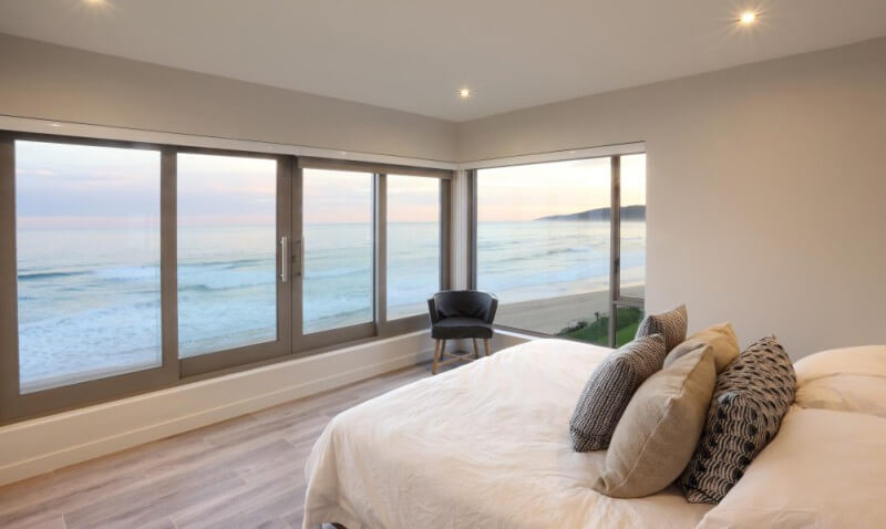 Bedroom overlooking the ocean with hardwood flooring.