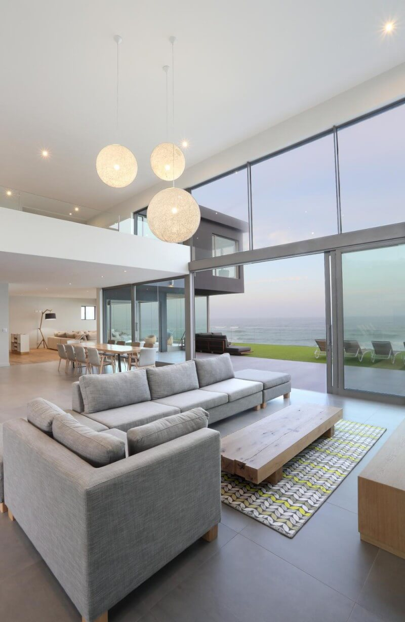 Living area of a modern house with glass windows and walls, modern decor, and a view of the ocean.
