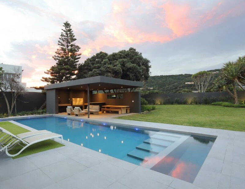 A pool in the backyard of a beach home with concrete decking and a pergola.