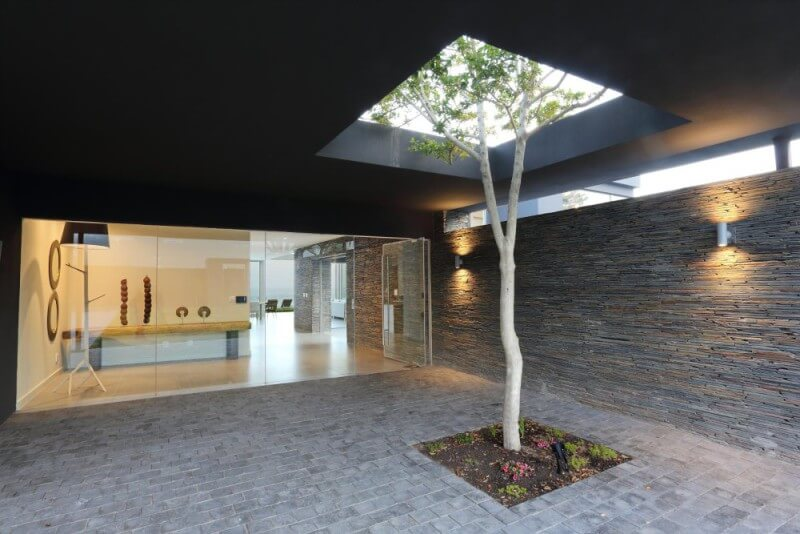 Covered courtyard of a modern home with a glass looking room and tree growing through the roof.