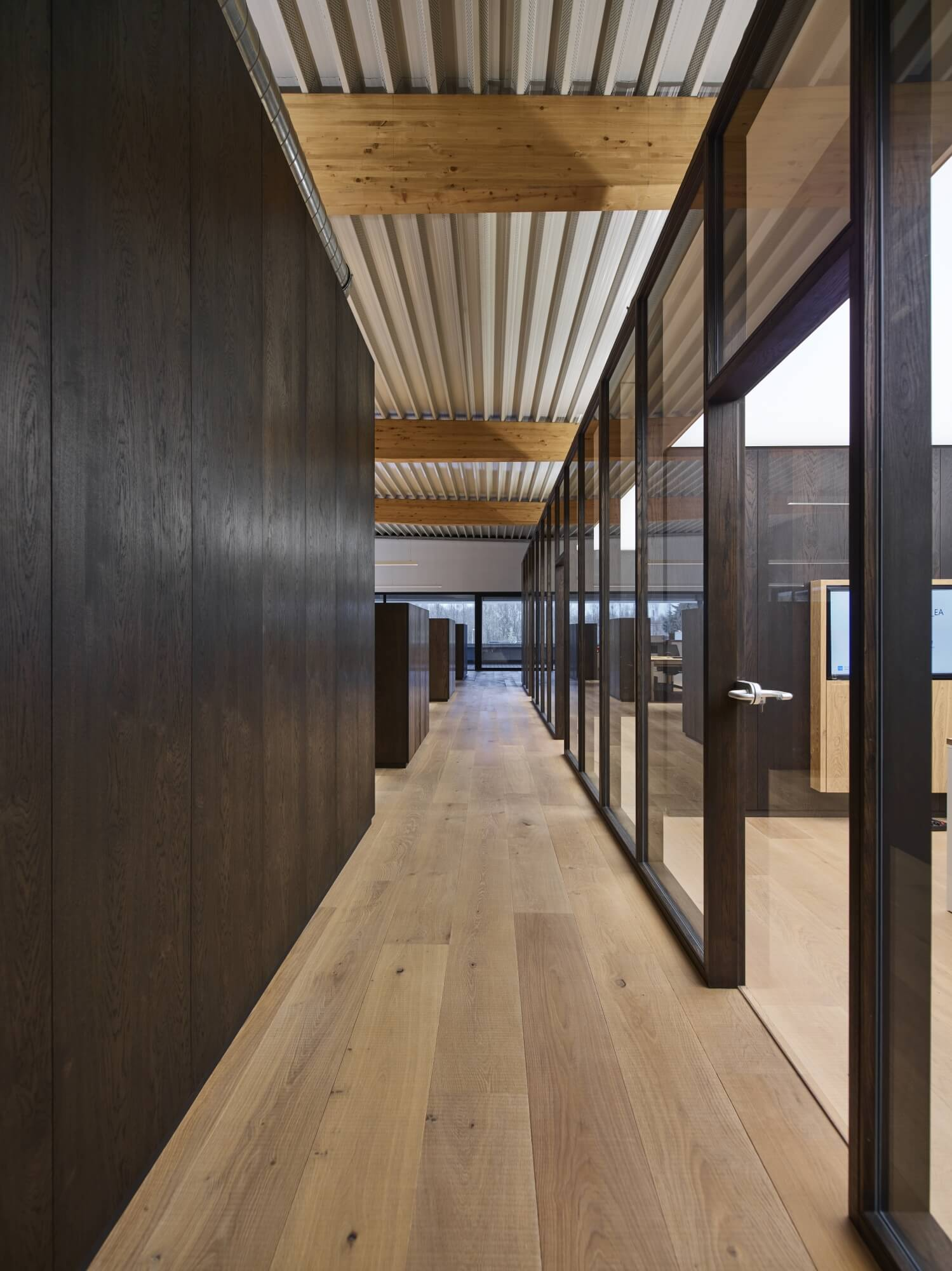 A hallway with wood floors, wood wall panels and glass office barriers at the Rubio Monocoat headquarters.