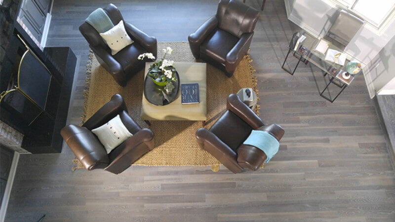 A fumed hardwood floor in a living room with chairs around it.