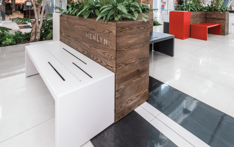 A wooden planter box with a dark matte finish and a white benchs eat pressed against it.
