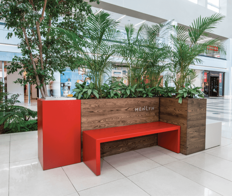 A brown wood planter box inside a mall with a bright red bench and trash can beside it.