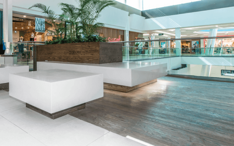 Wooden planter boxes and seating in a mall are finished with a matte wood finish.