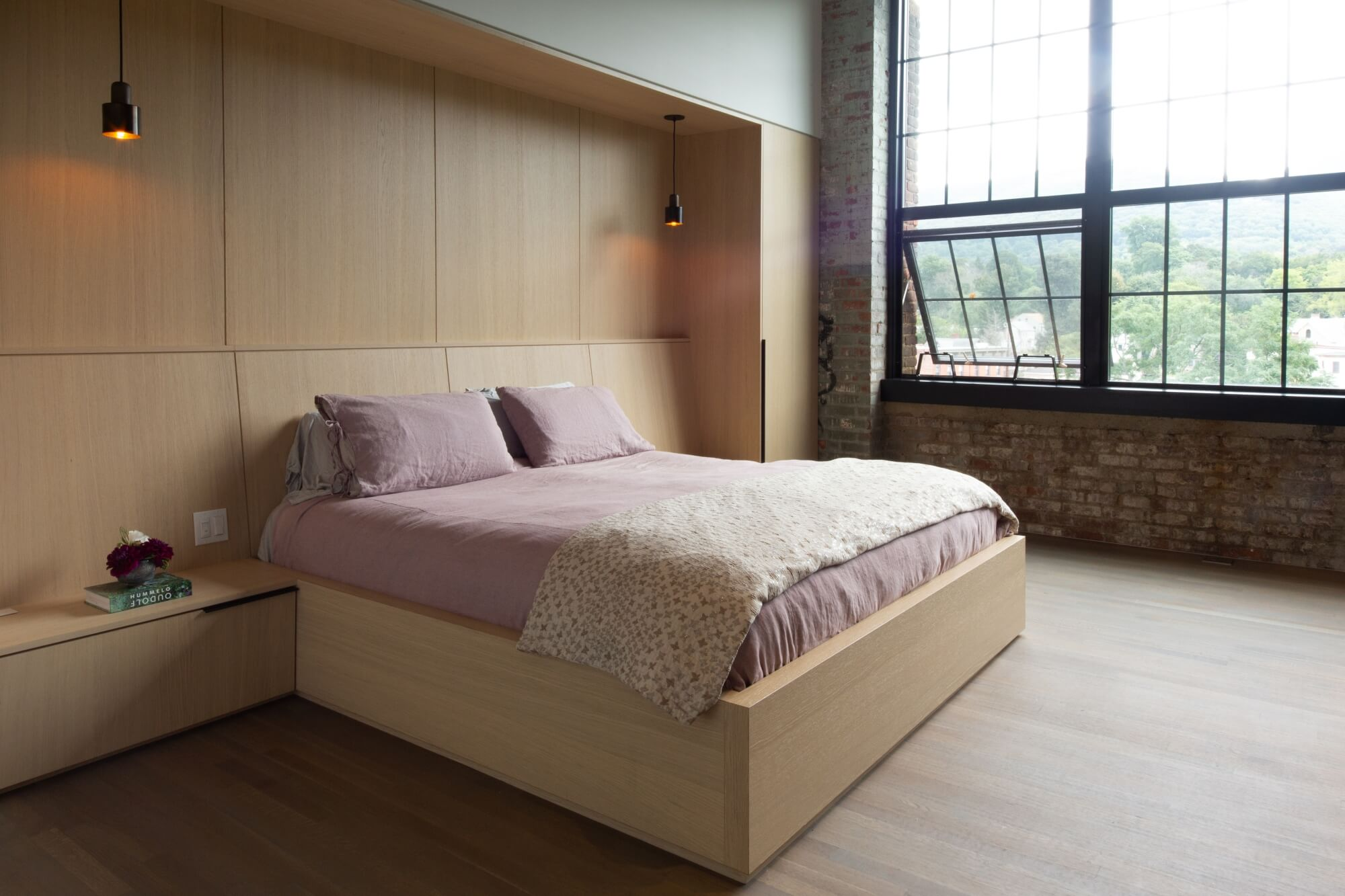 New York loft bedroom with hardwood flooring and a wooden bed frame and headboard.