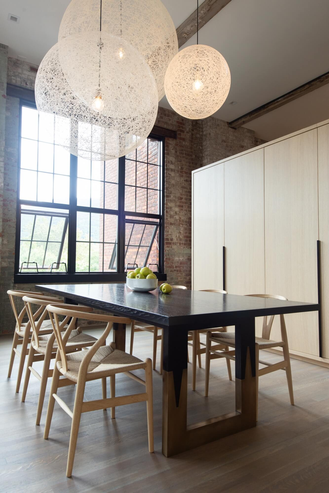 New York loft with circular lights above dining table in a room with hardwood flooring.