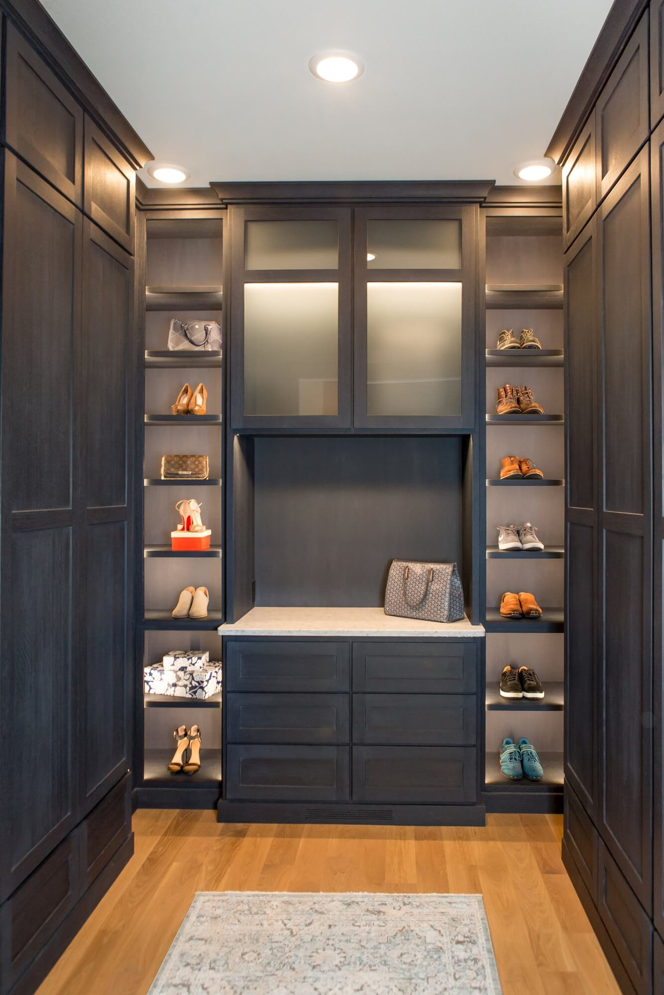 Luxury closet with shoe shelving, dark cabinetry and oak wood flooring.